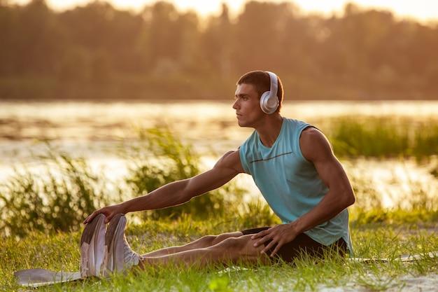 Jeune homme athlétique travaillant, s'entraînant au bord de la rivière à l'extérieur.