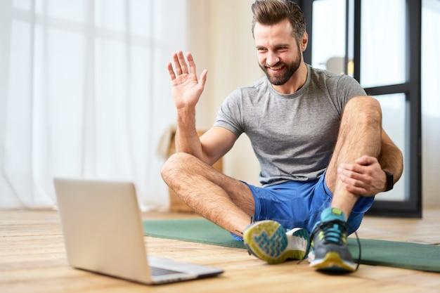 Jeune homme athlétique utilisant un ordinateur portable pour la communication en ligne à la maison