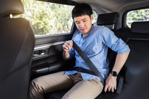 Jeune homme attachant une ceinture de sécurité alors qu'il était assis sur le siège arrière de la voiture