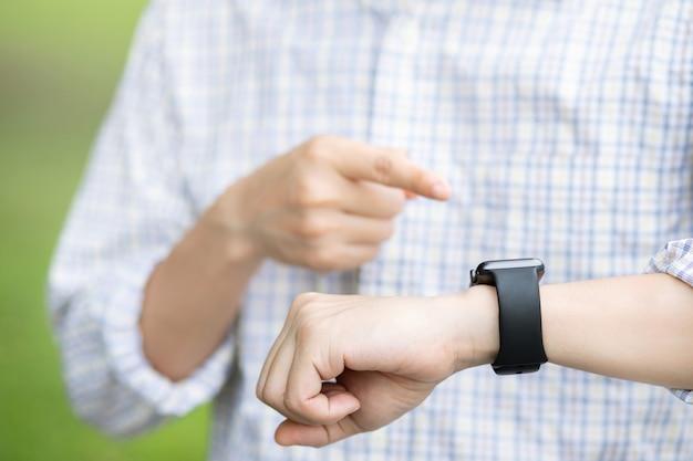 Jeune homme attend avec impatience la minuterie en regardant l'horloge. réunion prendre rendez-vous dans le concept de limite de temps. montre-bracelet