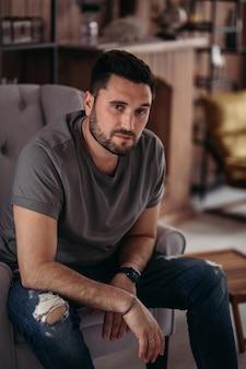Le jeune homme attirant se détend à la maison
