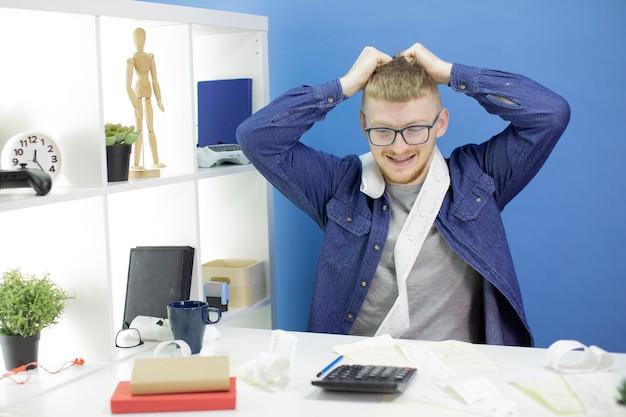 Jeune homme a attrapé sa tête en regardant la calculatrice gérant seul le budget national