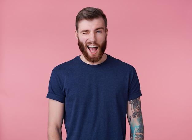 Jeune homme attrayant à la barbe rousse aux yeux bleus, vêtu d'un t-shirt bleu, regardant la caméra et clignant de l'œil, a l'air cool isolé sur fond rose.
