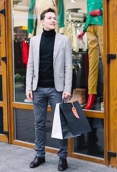 Un jeune homme attrayant, debout à l'extérieur du magasin, tenant des sacs à provisions à la main