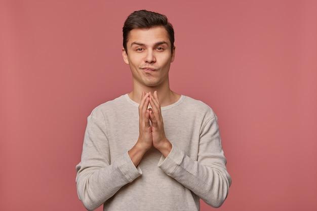Jeune homme attrayant porte des manches longues décontractées, fait un vœu, espère bonne chance et montre le geste prié, se tient sur fond rose.