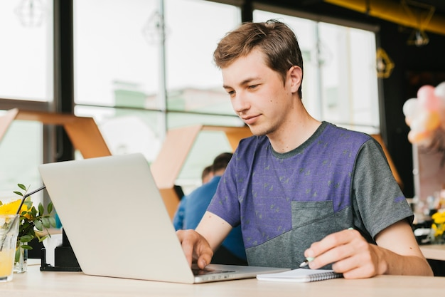 Jeune homme au café travaillant sur un ordinateur portable
