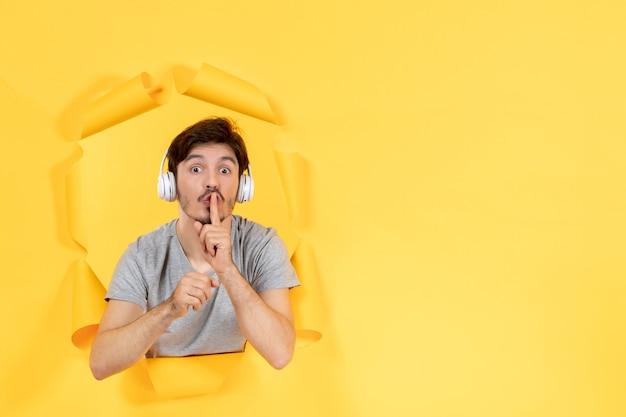 Jeune homme au casque sur fond de papier jaune son ultrasonore
