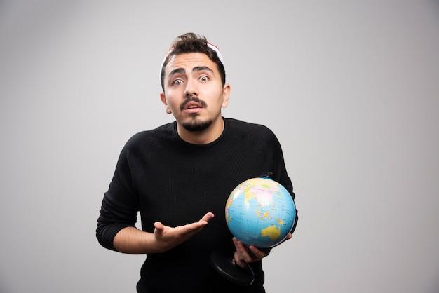 Jeune homme au chapeau du père noël montrant un globe.