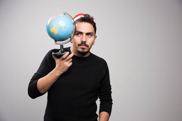 Jeune homme au chapeau du père noël tenant un globe.