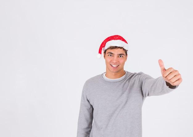 Jeune homme au chapeau de noël avec le pouce vers le haut