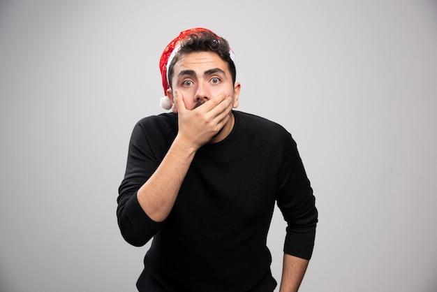 Un jeune homme au chapeau rouge du père noël couvrant sa bouche avec la main.