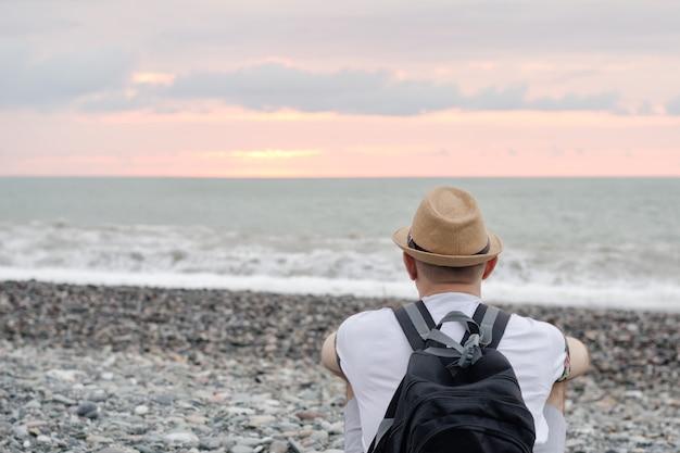 Jeune homme au chapeau et avec sac à dos assis sur la plage. mer et ciel coucher de soleil. vue arrière