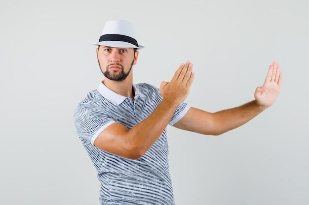 Jeune homme au chapeau, t-shirt rayé levant les bras de manière préventive et ayant l'air flexible, vue de face.