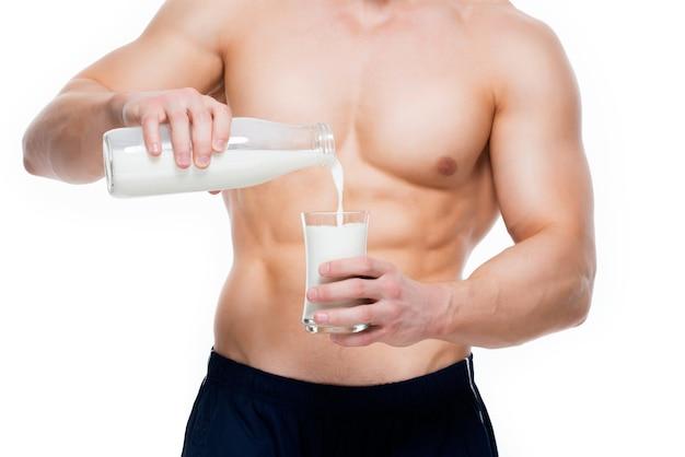 Jeune homme au corps parfait, verser du lait dans un verre - isolé sur un mur blanc.
