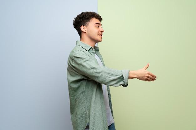 Jeune homme au cours d'une poignée de main bleue et verte après une bonne affaire