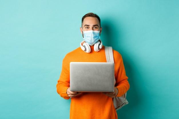 Jeune homme au masque facial à l'aide d'un ordinateur portable, debout sur un mur turquoise clair