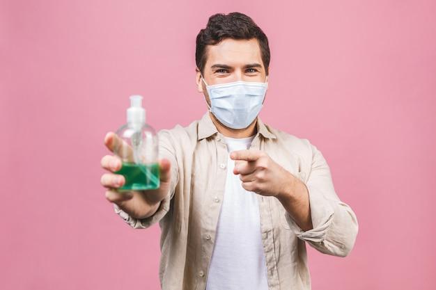 Jeune homme au masque facial stérile isolé. coronavirus pandémique épidémique 2019-ncov sars covid-19 virus virus concept. bouteille avec un désinfectant liquide antibactérien à base d'alcool.