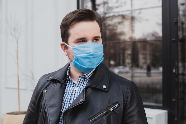 Jeune homme au masque sur un fond de café fermé, coronavirus, maladie, infection, quarantaine, masque médical