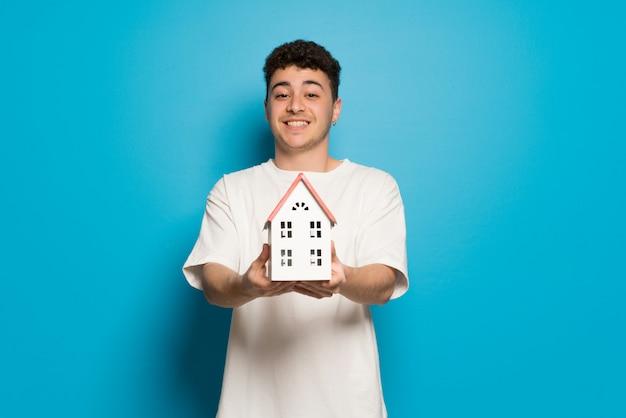 Jeune homme au mur bleu tenant une petite maison