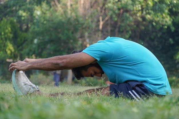 Jeune homme au parc faisant des exercices matinaux