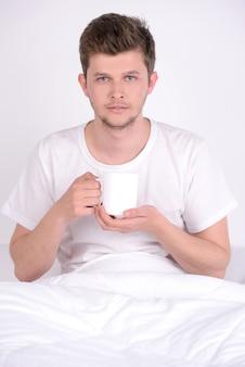 Le jeune homme au petit déjeuner au lit à la maison.