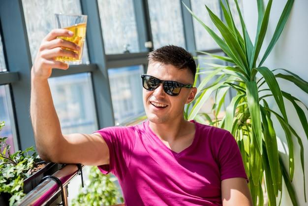 Jeune homme au pub. boire de la bière, manger de la pizza.