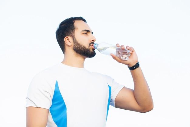 Jeune homme au repos et à l'eau potable après un footing