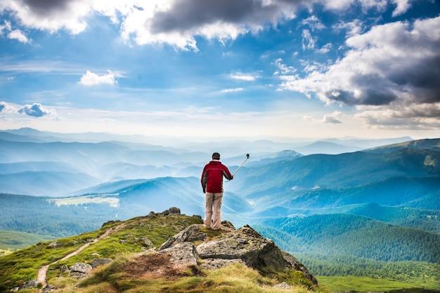 Jeune homme au sommet de la montagne prenant une photo avec un appareil photo sur un bâton de selfie