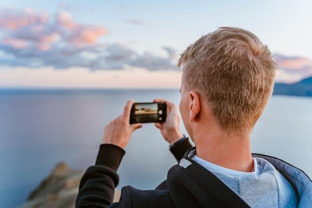 Un jeune homme au sommet d'une montagne prend une photo sur son smartphone avec une vue imprenable sur le coucher de soleil