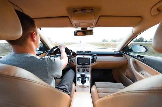 Le jeune homme au volant de la voiture moderne sur route goudronnée