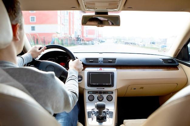 Le jeune homme au volant de la voiture sur route asphaltée