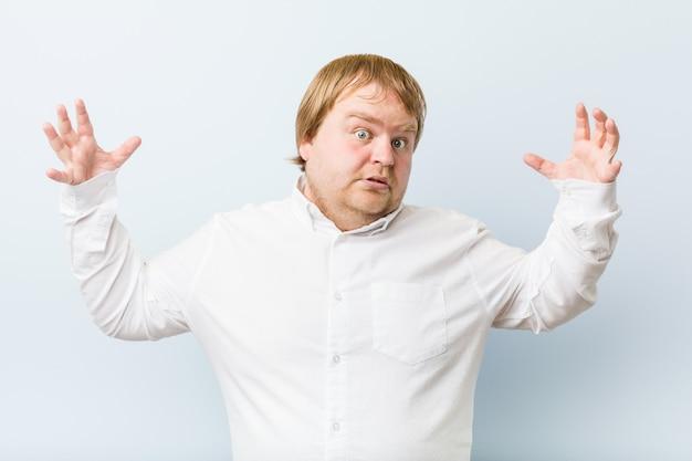 Jeune homme authentique, gros homme rousse, reçoit une agréable surprise, excité et levant les mains.