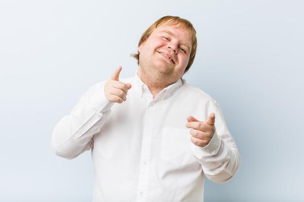 Jeune homme authentique, gros homme rousse, sourires joyeux pointant vers l'avant.