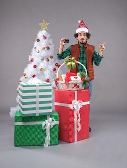 Jeune homme autour de cadeaux de noël sur fond gris