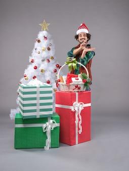 Jeune homme autour des cadeaux de vacances sur gris
