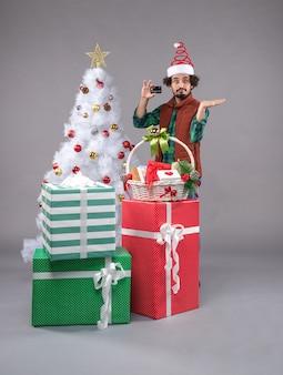 Jeune homme autour des cadeaux de vacances sur sol gris