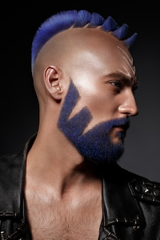 Jeune homme aux cheveux bleus et maquillage créatif et cheveux.