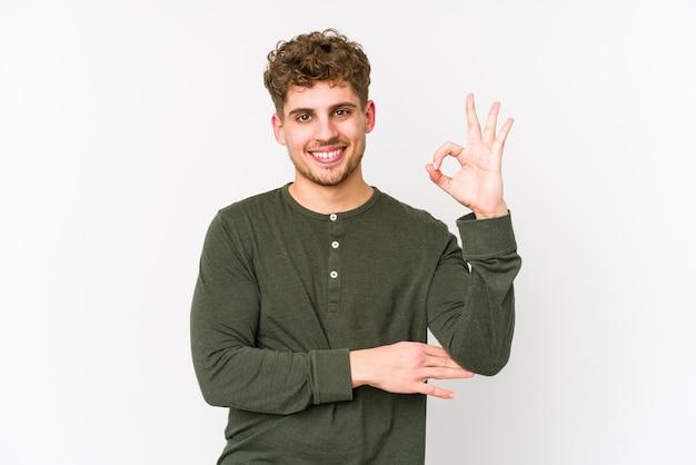 Jeune homme aux cheveux bouclés blonds fait un clin d'œil et détient un geste correct avec la main.