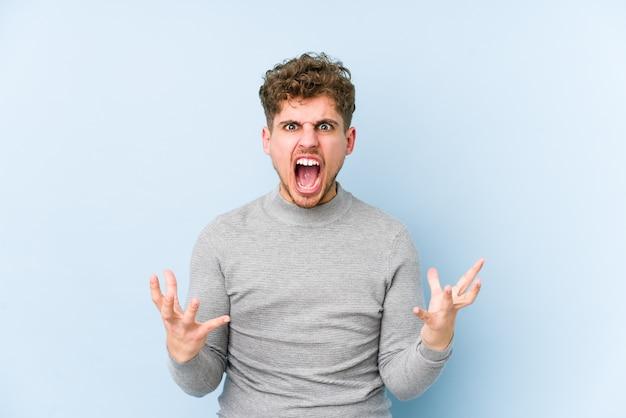 Jeune homme aux cheveux bouclés blonds hurlant de rage
