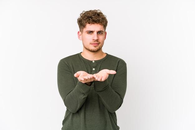 Jeune homme aux cheveux bouclés blonds tenant quelque chose avec des paumes, offrant à la caméra