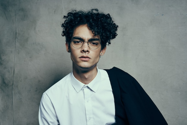 Jeune homme aux cheveux bouclés en chemise costume classique modèle de studio de photographie sur fond de tissu