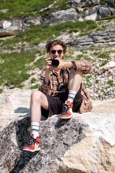 Un jeune homme aux cheveux bouclés prenant des photos à l'aide d'un appareil photo dans la nature, assis sur la pente d'une colline rocheuse