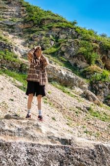 Un jeune homme aux cheveux bouclés prenant des photos à l'aide d'un appareil photo dans la nature, restant sur la pente d'une colline rocheuse