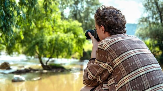 Un jeune homme aux cheveux bouclés prenant des photos à l'aide d'un appareil photo dans la nature, la rivière et la verdure à proximité