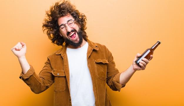 Jeune homme aux cheveux fous en mouvement, buvant une bière