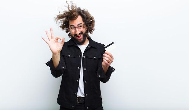 Jeune homme aux cheveux fous en mouvement et carte de crédit
