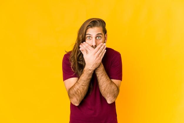 Jeune homme aux cheveux longs a l'air choqué couvrant la bouche avec les mains.