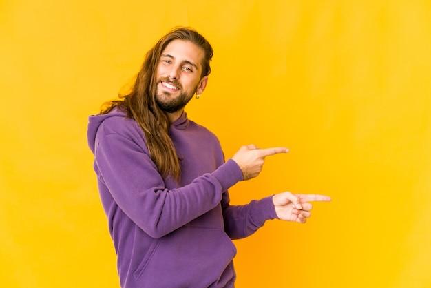 Jeune homme aux cheveux longs a l'air excité en pointant avec l'index loin.