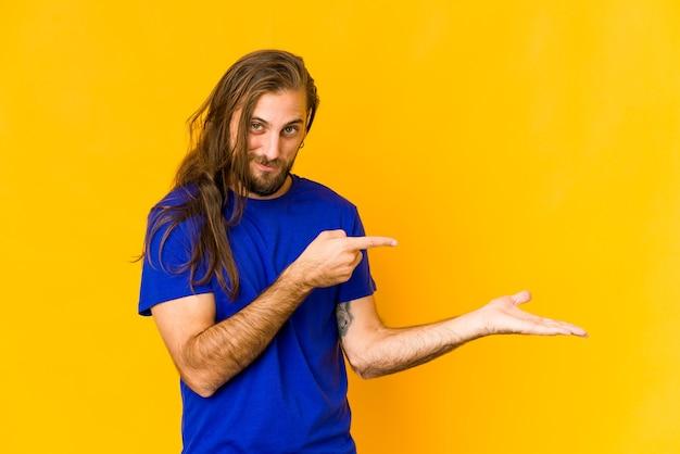 Jeune homme aux cheveux longs a l'air excité tenant un espace de copie sur la paume