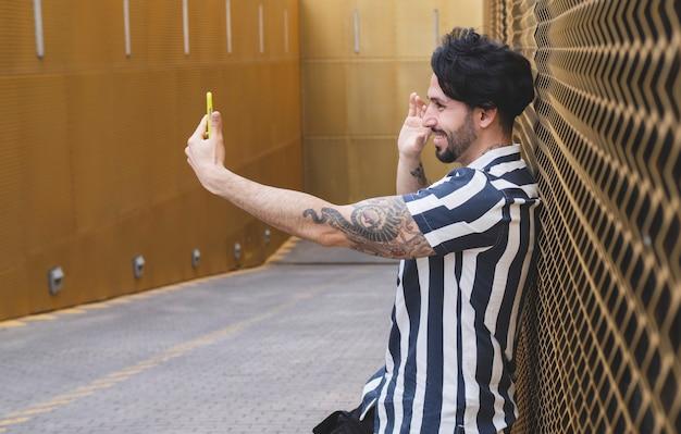 Jeune homme aux cheveux longs et aux tatouages, fait du selfi sur un mur doré